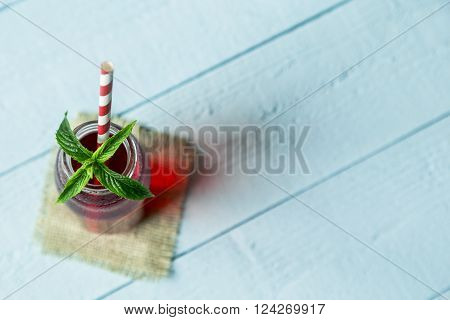 Top view of a jar filled with organic raspberry juice with striped red and white drinking straw and fresh mint leaves in it placed on burlap coaster on wooden boards surface