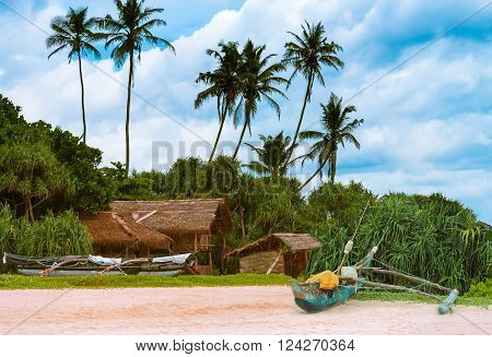 The hut of bamboo and fishing boats on the beautiful sandy beach on the island of Sri Lanka.