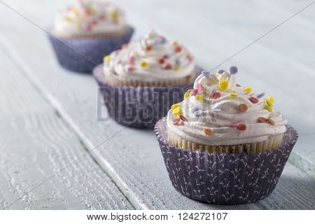 Three cup cakes with colorful sprinkles on a wooden table