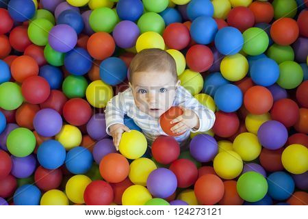 8 month baby boy playing in the playground balls pool. High view shot