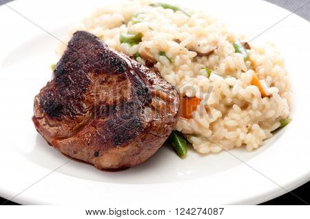 medium rare grilled beef tenderloin steak with vegetable risotto