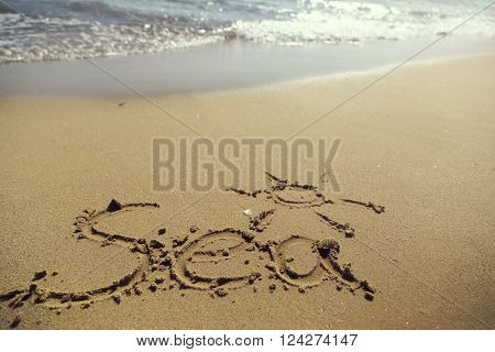 Word sea handwritten in sand on the beach next to the waterline