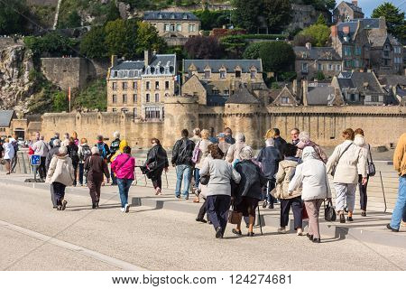 FRANCE, MONT SAINT MICHEL - SEPTEMBER 26: Old people visiting Mont Saint Michel monastery, Brittany, France on September 26, 2015