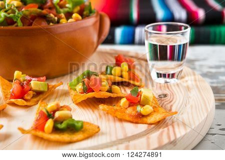 Close up of nachos chips and tequila with a poncho on background ** Note: Shallow depth of field