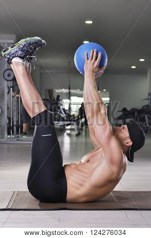 Handsome Powerful Athletic Man Performing Crunches With Medicine Ball. Strong Bodybuilder With Perfe
