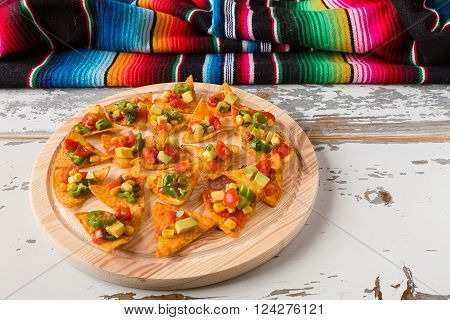 Nachos chips with vegetables on a chopping board and a poncho over an old wooden table