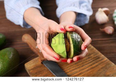 Female hands holding halved  avocado, close up