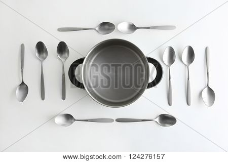 Saucepan and silver spoons, top view