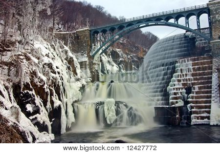 View of reservoir spillway in winter covered in snow and ice.