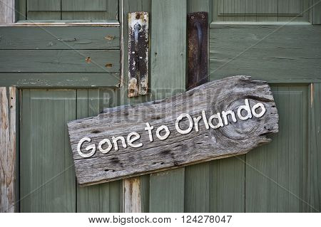 Gone to Orlando sign on old green doors.