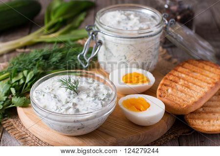 Yoghurt sauce with herbs and eggs on a wooden table