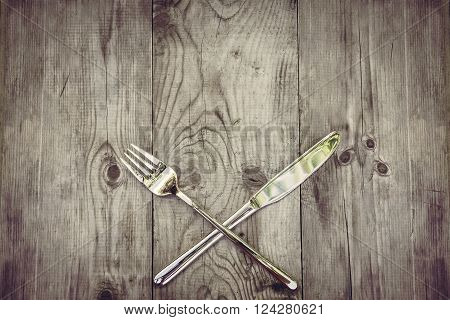 Rustic wood background with silver cutlery. View from above on  rustic wooden table and crossed silvery cutlery. Can be used as background menu for restaurant with Mediterranean and Caribbean cuisine