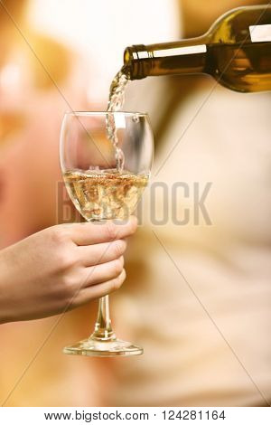 Pouring white wine into glass at hen-party, close up