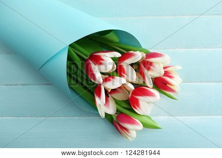 Bouquet of variegated tulips wrapped in paper on blue wooden background