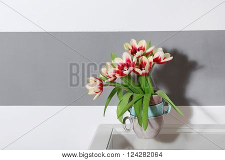 Bouquet of variegated tulips near striped wall