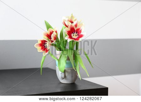 Bouquet of variegated tulips on black table near striped wall