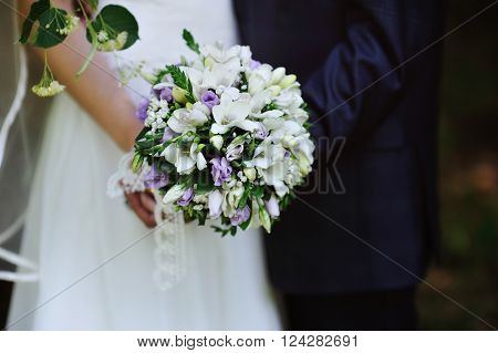 beautiful white wedding bouquet at bride's hands