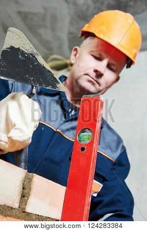 bricklayer at work with level and trowel