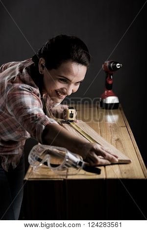 Woman Measuring A Wooden Board With A Tape Measure