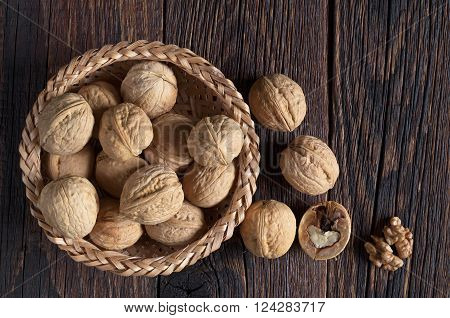 Walnut in bowl and walnuts kernels on dark wooden table top view