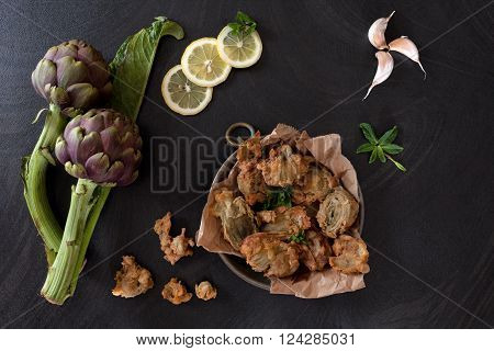 Fried roman artichokes on kitchen paper, decorated with slices of lemon, mint leaves and garlic.