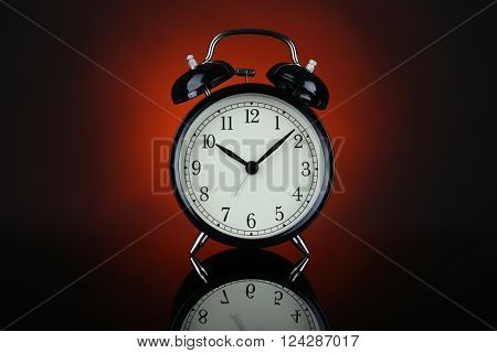 Alarm clock on a dark red background.