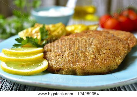 Viennese schnitzel on a blue plate on rustic background.
