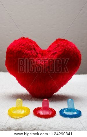 contraception love and birth control. Colorful condoms and red heart shaped little pillow