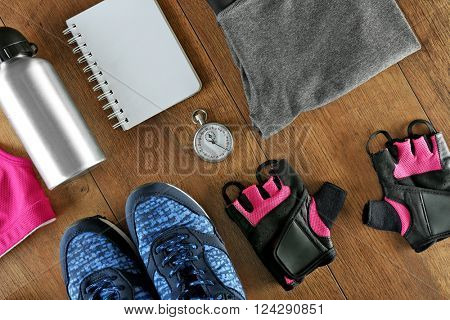 Athlete's set with female clothing, bottle of water, stopwatch and notebook on wooden background