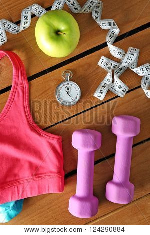 Athlete's set with female clothing, equipment and apple on wooden background