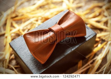 Brown leather bow tie with special packaging on a thatch, close up