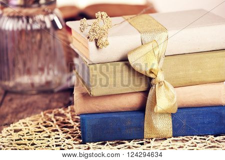 Stack of old books tied with yellow ribbon on a table, close up