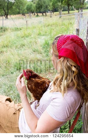 A woman with a chicken on her lap looks longingly into the distance