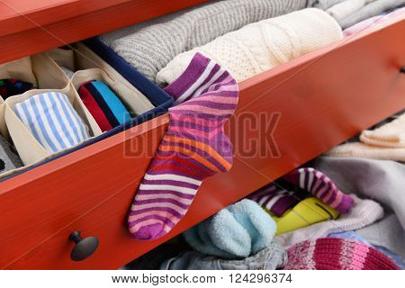 Woman's sock and pile of clothes in open drawer, close up