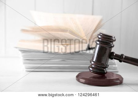 Gavel with open book and stack pf paper on wooden table closeup