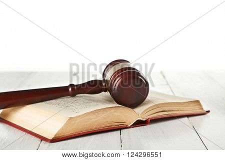 Gavel and book on wooden table on white background
