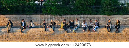 PARIS, FRANCE - MAY 13: People enjoy sunset light by River Seine on May 13, 2015 in Paris. With the population of 2M, Paris is the capital and most-populous city of France