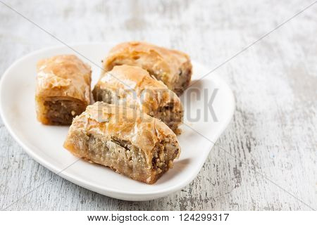 Baklava with walnut on a white wooden background