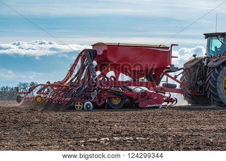 Close view on the tractor harrowing the field in spring season