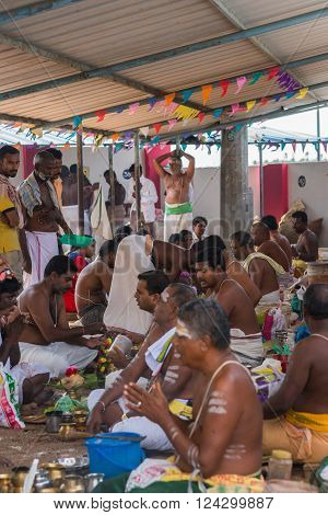 Trichy India - October 15 2013: Ten half-naked gurus in a line sit on the right. Most of them have a paying client in front of them. Rituals are performed. Onlookers follow the proceedings. Cacophony of mantras.