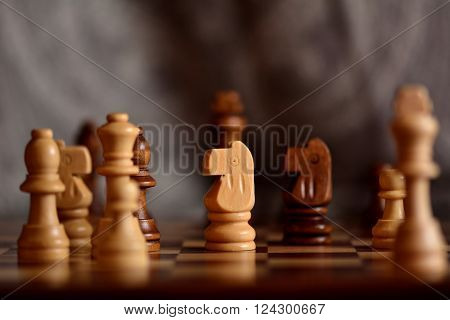 Wooden chess pieces on board. Chessmen on board during play, with focus on white knight and bokeh