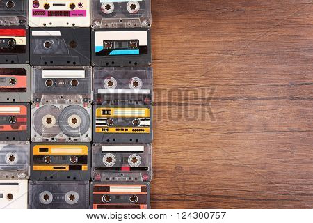 Collection of audio cassettes on wooden table background, copy space