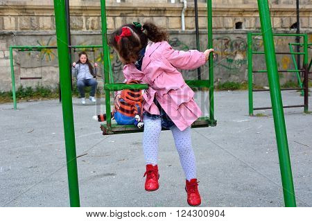 Young girl with toy on swing looking back at big sister. Children play on swings in a playground in Baku, Azerbaijan, with the smallest looking over her shoulder