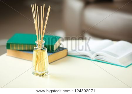 Handmade reed freshener with books on white table in living room, close up