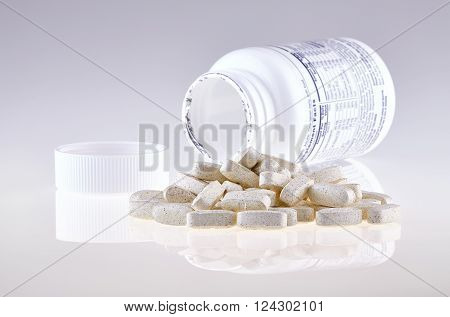 Pills of nutritional supplement spilled out open container on white background.