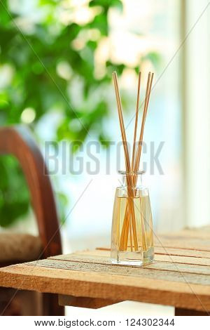Handmade reed freshener on wooden table in living room, close up