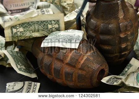 torn and crumpled money and hand grenades indicating an explosive economy and economic destruction