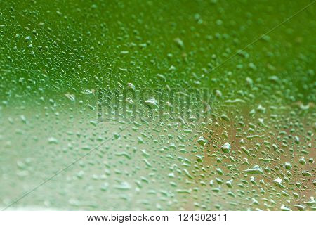 drops of water flow down the glass after rain, background for  design