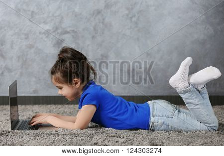 Little girl using laptop on fur carpet against grey wall background