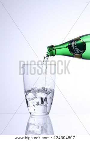 KUALA LUMPUR, MALAYSIA - Feb 17, 2016 pouring perrier mineral water into glass with ice cube